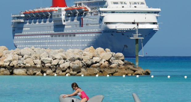 Carnival Cruise Lines' guests have fun on a water toy off the beach at Half Moon Cay in the Bahamas while a Carnival ship lies at anchor in the background. Half Moon Cay, a private Bahamian island offering white-sand beaches and numerous watersports opportunities, is featured on certain Carnival Cruise LinesÕ itineraries. Photo by Andy Newman/Carnival Cruise Lines.